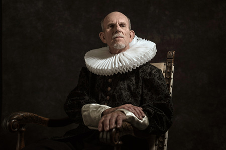 golden age: Official portrait of historical governor from the golden age. Sitting in chair. Studio shot against dark wall.