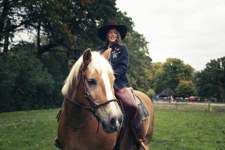 femme a cheval: Sourire occidentale femme de style �quitation dans la campagne.