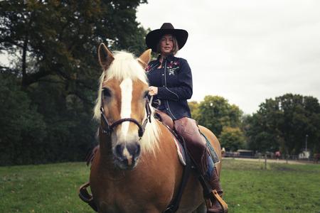 femme et cheval: Sourire occidentale femme de style équitation dans la campagne.