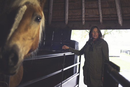 looking towards camera: Woman standing at fence in stable. Horse looking towards camera.