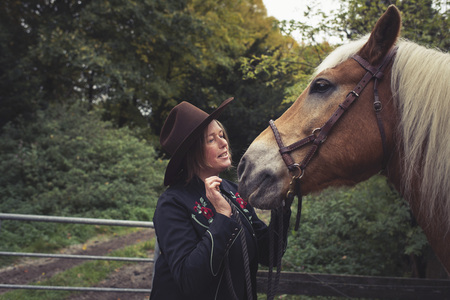 petting: Cowgirl petting the nose of her horse.