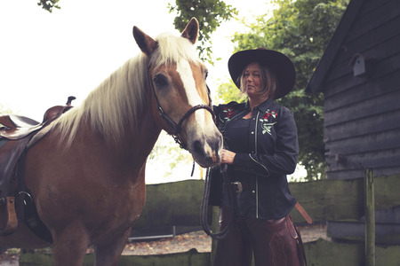 stroking: Woman in western style stroking her horse.