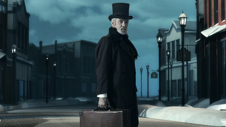 dickens: Dickens Scrooge Man in Old Winter Street. Holding Suitcase. Stock Photo