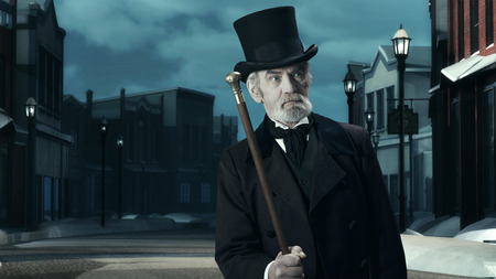 dickens: Dickens Scrooge Man in Old Winter Street. Holding Cane. Stock Photo