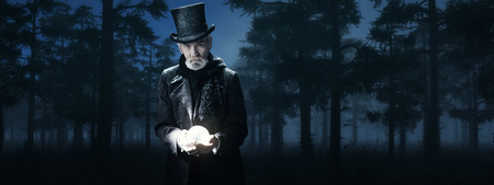 Dickens Scrooge Man Holding Illuminated Sphere in Foggy Winter Forest at Night.