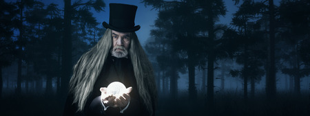 illusionist: Illusionist Holding Illuminated Sphere in Foggy Winter Forest at Night.