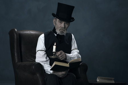 dickens: Dickens Scrooge Man Sitting in Chair with Book by Candlelight.