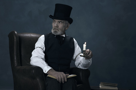retro dark: Dickens Scrooge Man Sitting in Chair with Book by Candlelight.