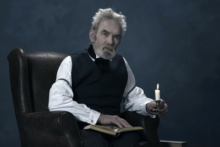 dickens: Alert Dickens Scrooge Man Sitting in Chair with Book Holding Candlestick.
