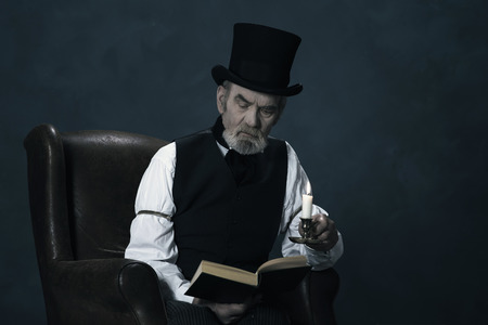 dickens: Dickens Scrooge Man Sitting in Chair Reading Book by Candlelight.