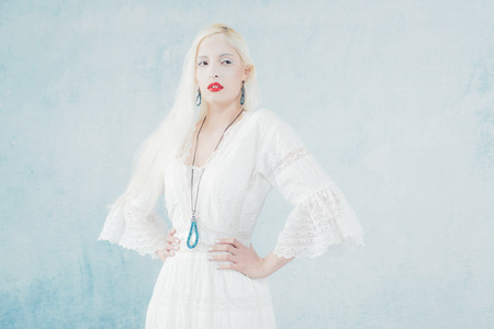 frozen winter: Snow Princess with Red Lipstick Wearing Necklace and Earrings. Against Light Blue Wall.