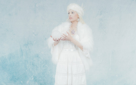 snow ball: Snow Queen Holding Snow Ball. Fashion in White Fur Against Light Blue Wall.