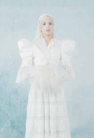sleeve: Snow Princess in White Dress Warming Hands in Fur Sleeve. Against Light Blue Wall.
