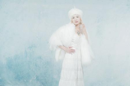 queen blue: Snow Queen Fashion in White Fur Against Light Blue Wall.