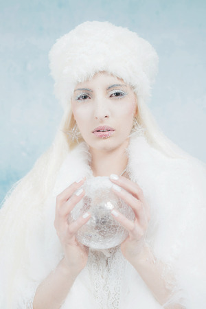 queen blue: Snow Queen Holding Glass Sphere. Wearing White Fur. Against Light Blue Wall.