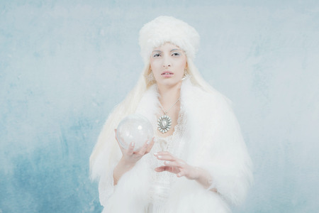 glass sphere: Snow Queen Holding Glass Sphere. Wearing White Fur. Against Light Blue Wall.