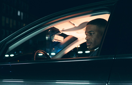 road traffic: Side view of young man in car at night.