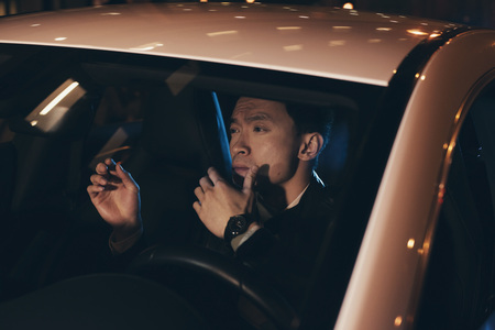 young man portrait: Asian man in car at night.