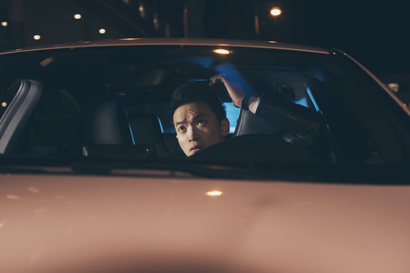 young man portrait: Asian man in car doing his hair.