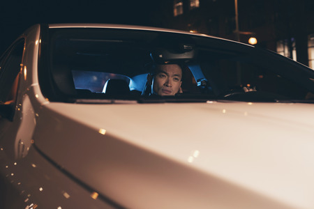 young man portrait: Young asian man sitting in car at night. Stock Photo