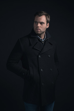 stubbly: Stubbly bearded young man wearing dark blue winter coat.