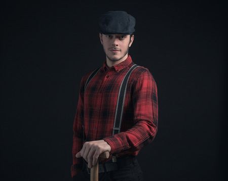stubbly: Fashionable farmer in red checkered shirt holding pitchfork.
