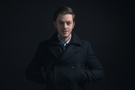 stubbly: Young man with stubbly beard wearing dark blue winter jacket.