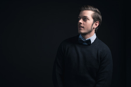 shirt: Man wearing dark blue sweater and light blue shirt with bow tie.