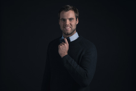 stubbly: Smiling man wearing dark blue sweater and light blue shirt holding bow tie.