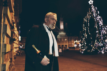 dapper: Man in tuxedo with bottle of champagne on town square at night.