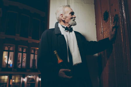 elegant party: Man in tuxedo with bottle of champagne knocking on door at night.
