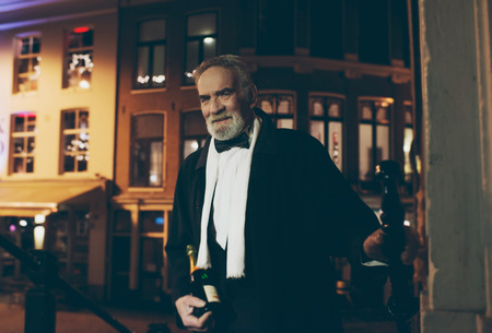 dapper: Smiling man in tuxedo with bottle of champagne at door at night. Stock Photo