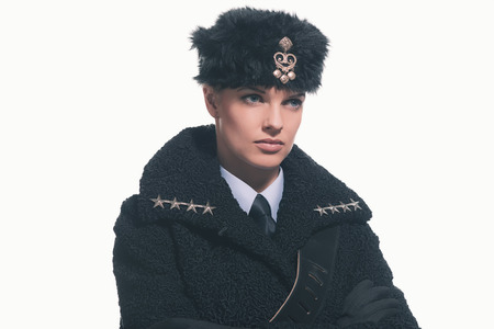 Female guard wearing retro russian winter costume with hat isolated against white. Stock Photo