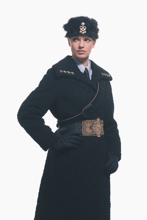 russian hat: Female guard wearing retro russian winter costume with hat isolated against white. Stock Photo