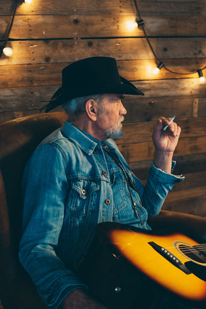 senior smoking: Smoking senior country and western guitarist with beard sitting in chair. Stock Photo