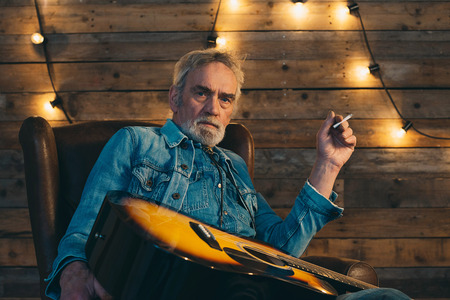 senior smoking: Smoking senior guitarist with beard sitting in chair in front of wooden wall with light bulbs.