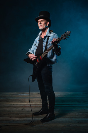 heavy metal: Heavy metal senior man with electric guitar in front of dark blue background.