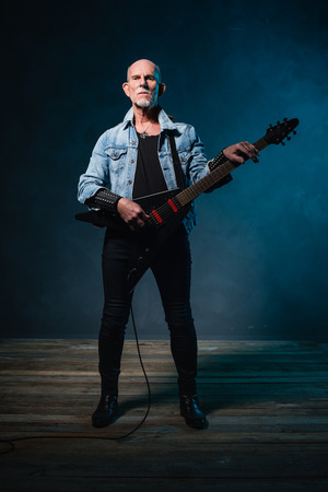 heavy metal: Bald heavy metal senior man with electric flying-v guitar in front of dark blue background. Stock Photo