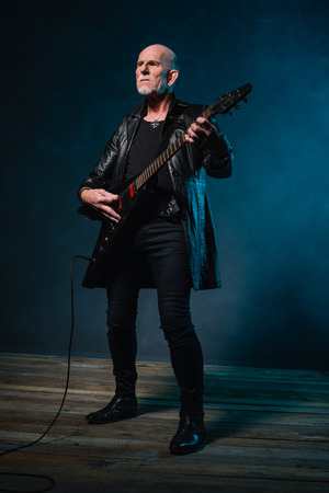 heavy metal: Bald heavy metal senior man with electric guitar in front of dark blue background. Stock Photo