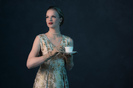 young girl nude: Smiling chique vintage 1950s fashion woman holding white tea cup. Stock Photo