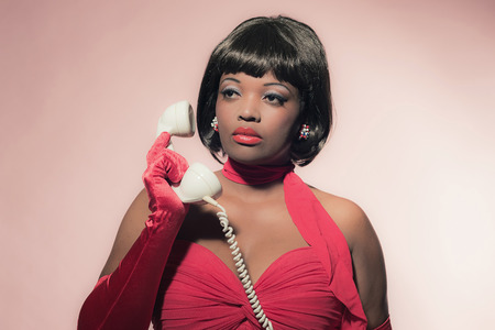 60's: Retro 60s fashion african woman in red dress holding earpiece of telephone.