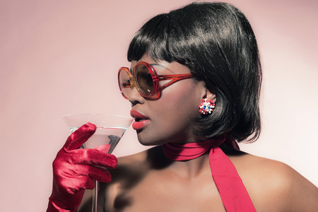 60's: Retro 60s fashion african woman with sunglasses holding cocktail glass. Stock Photo