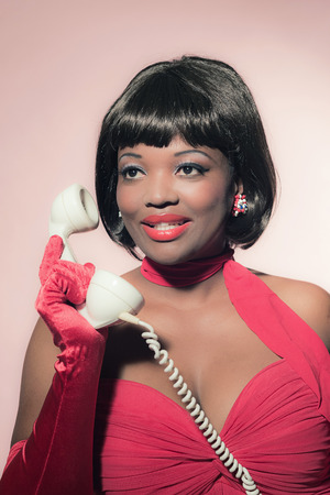 earpiece: Retro 60s fashion african woman in red dress holding earpiece of telephone.