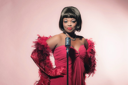 american music: Retro 60s female african soul singer in red dress against pink background.