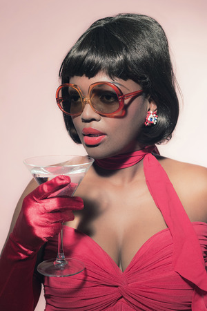60s: Retro 60s fashion african woman with sunglasses holding cocktail glass. Stock Photo