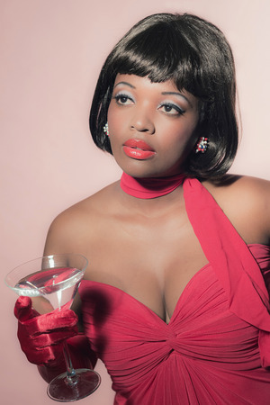 60's: Vintage 60s fashion african woman in red dress holding cocktail glass.
