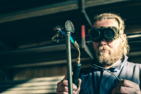 Man with goggles soldering iron pipe