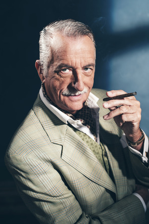 senior smoking: Cigar smoking retro 1940 senior businessman. Studio shot. Stock Photo
