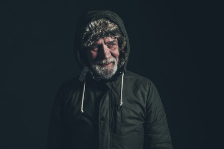 gray beard: Senior man with gray beard wearing dark green winter coat with hoody. Stock Photo