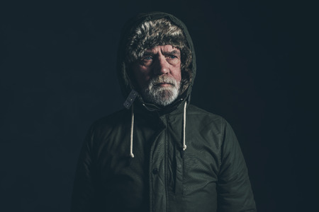 hoody: Senior man with gray beard wearing dark green winter coat with hoody. Stock Photo
